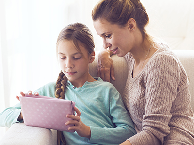mother using ipad with daughter